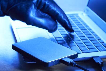 Photo pour Cyber Criminal Downloading Data Onto Portable Hard Drive - image libre de droit