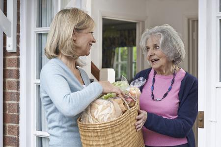 Foto für Female Neighbor Helping Senior Woman With Shopping - Lizenzfreies Bild