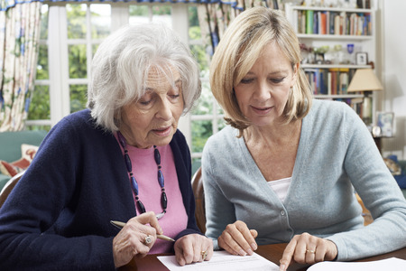 Photo pour Female Neighbor Helping Senior Woman To Complete Form - image libre de droit