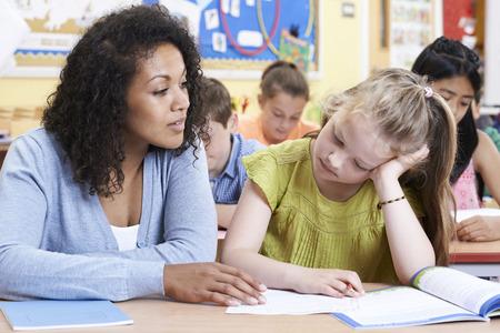 Foto de Teacher Female Elementary School Pupil With Problem - Imagen libre de derechos