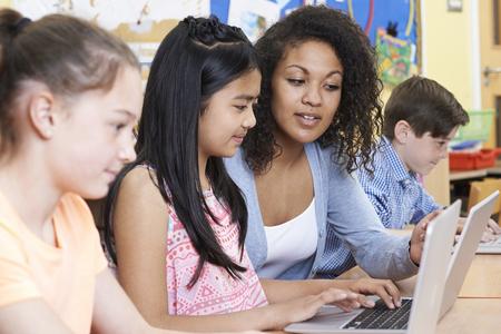 Foto de Teacher Helping Group Of Elementary School Children In Computer Class - Imagen libre de derechos