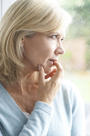 Photo for Sad Mature Woman Suffering From Agoraphobia Looking Out Of Window - Royalty Free Image