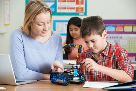 Photo pour Teacher With Pupils In Science Lesson Studying Robotics - image libre de droit