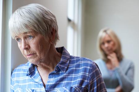 Foto de Serious Senior Woman With Adult Daughter At Home - Imagen libre de derechos