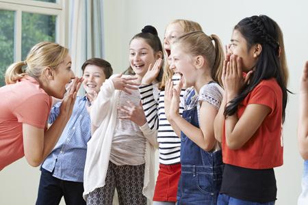 Foto de Group Of Children With Teacher Enjoying Drama Class Together - Imagen libre de derechos