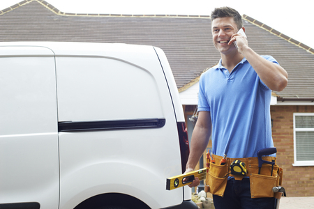 Photo for Builder With Van Talking On Mobile Phone Outside House - Royalty Free Image