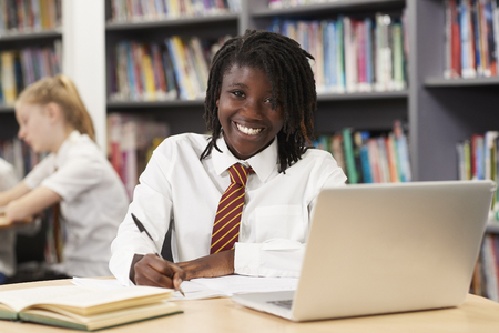 Photo for Portrait Of Female High School Student Wearing Uniform Working At Laptop In Library - Royalty Free Image