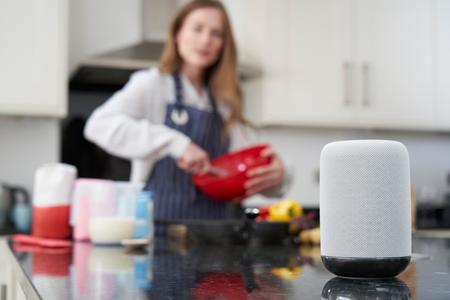 Photo pour Woman Preparing Meal At Home Asking Digital Assistant Question - image libre de droit