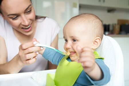 Photo for Smiling 8 month Old Baby Boy At Home In High Chair Being Fed Solid Food By Mother With Spoon - Royalty Free Image
