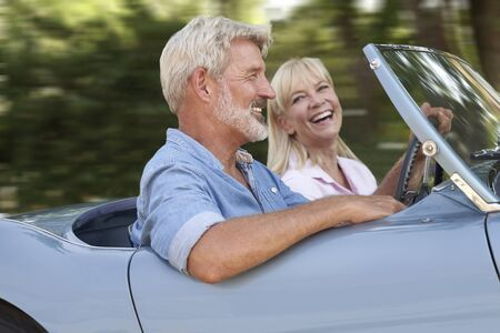 Photo pour Mature Couple Enjoying Road Trip In Classic Open Top Sports Car Together - image libre de droit