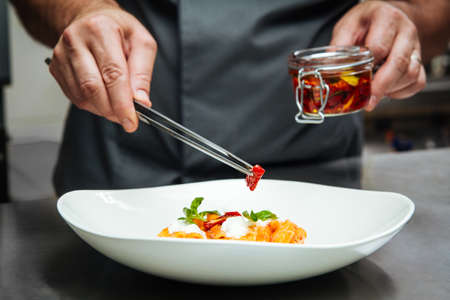 Photo pour Chef hand cooking pasta penne with mozzarella cheeze and sun-dried tomatoes in a white plate - image libre de droit