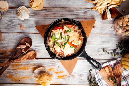 Photo pour Top view baked chicken with tomatoes and cheese in cast iron pan on the wooden decorated table - image libre de droit