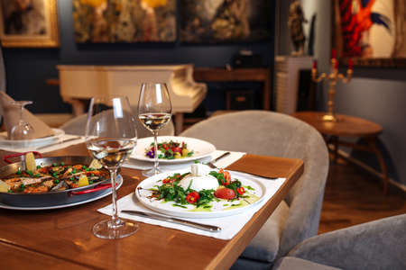 Photo pour Restaurant table served with spanish buratta tomato and peppers salads and paella - image libre de droit