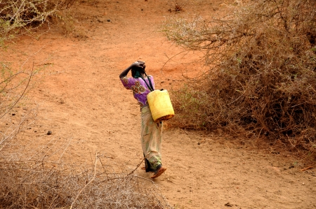 African woman carrying water cans