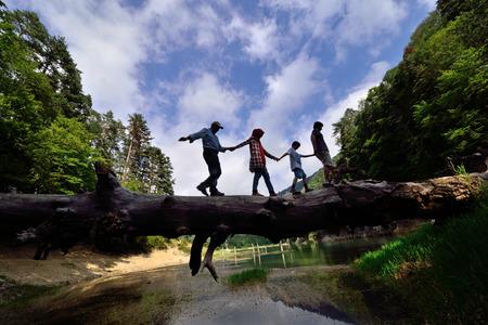 family walking on fallen tree in balance