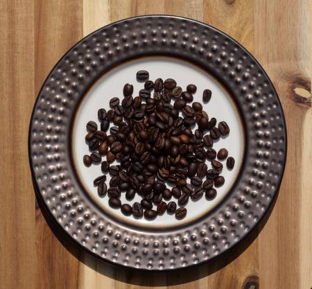 Dark roast coffee beans on decorative plate