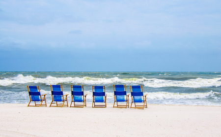 Tropical ocean beach shoreline, lined with beach chairs. Scenic travel destination location for relaxation and recreation.