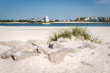 White sandy beach sand with rock and grass foliage. Distant view of Orange Beach, AL thru Gulf Coast bay waters. Scenic tourist travel destination.