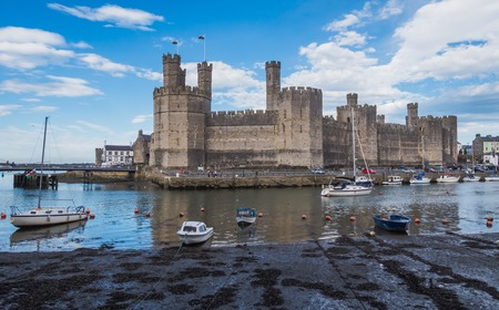 CAERNARFON, WALES - 29 SEPTEMBER 2013: Boats are anchored beside famous Caernarfon Castle with its polygonal towers where the Prince of Wales was invested in 1969