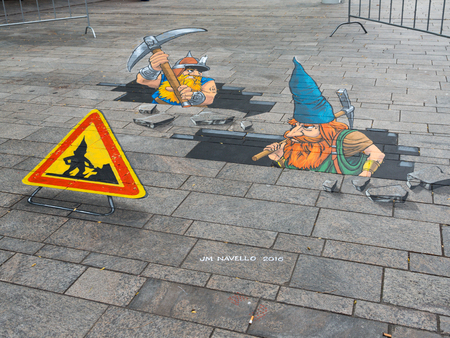 ALMERE, NETHERLANDS - 24 OCT. 2017: Street art of gnomes breaking through the street by an unknown artists shows the power of 3D optical illusion in Almere.