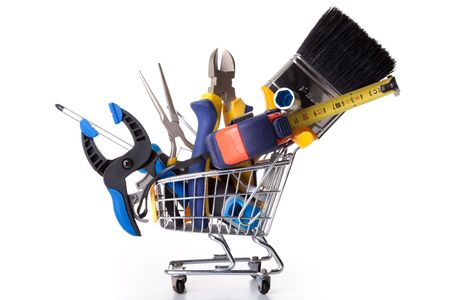 mix of construction tools inside a shopping cart (isolated on white)