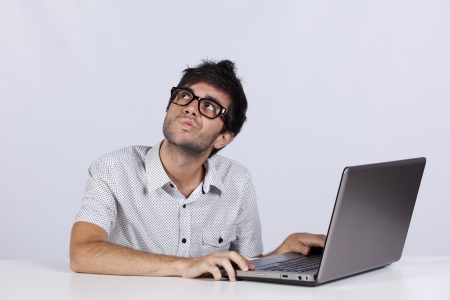 Young man thinking about a solution for a computer problem