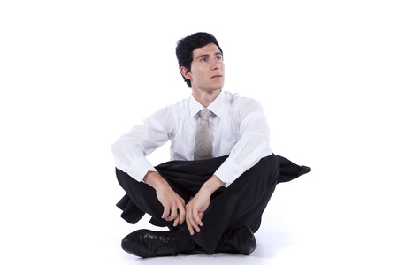 Young and modern businessman relaxing on the floor with his legs crossed (isolated on white)