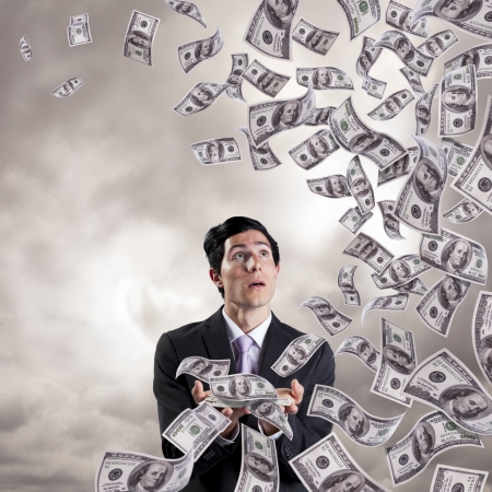 businessman loosing money from his hands (isolated on white)