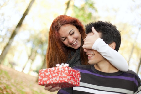 woman covering the eyes to his boyfriend with giving him a present (selective focus with shallow DOF)の写真素材