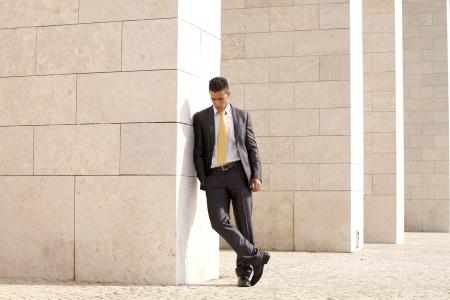 Photo pour Sad businessman next to some wall looking down - image libre de droit