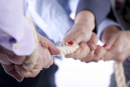 Group of woman hands pulling a rope competing with a man (selective focus)