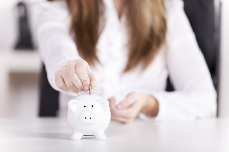 Woman inserting coins in the piggybank at her office (selective focus on the coin)