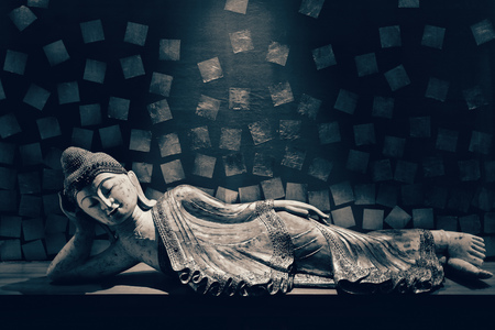 Antique carved wooden Buddha, reclining Buddha posture. selective focus.