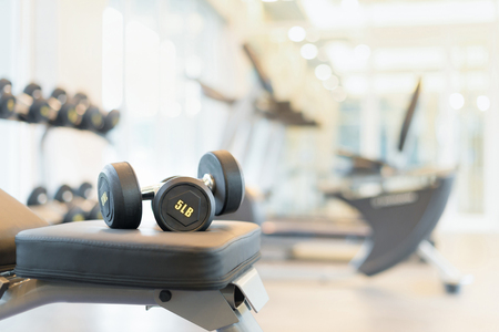 Foto de Two dumbbells on the exercise bench. Gym equipment. - Imagen libre de derechos