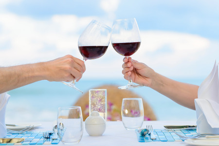 Photo pour Couple drinking wine in romantic dinner on twighlight, closeup. Selective focus, shallow depth of field. - image libre de droit