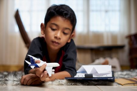Photo pour Boy lying in badroom playing with toy aeroplanes - image libre de droit