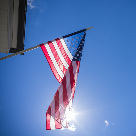American flag with star and stripes hanging on the house and proudly waving on the wind over a shiny sun on blue sky background