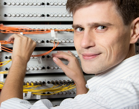 The engineer in a data processing center of ISP Internet Service Provider hold fiber patch cords