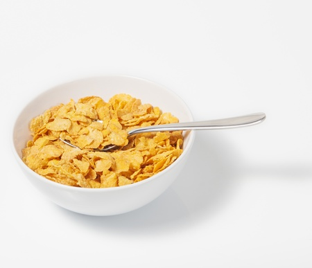 Corn flakes in deep plate with spoon.A Breakfast. High key.
