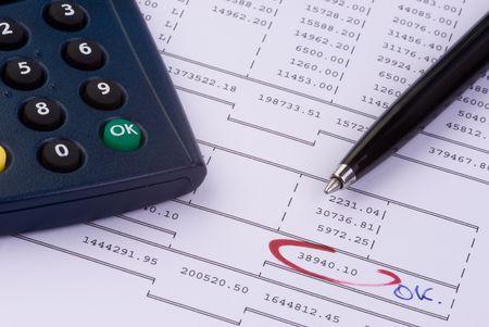a pen and a calculator on a balance sheet