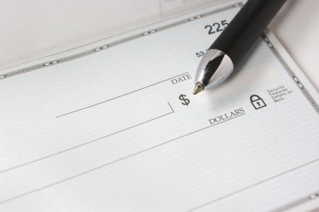 Photo pour A pen resting on a blank check. - image libre de droit