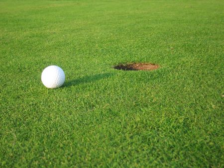 Golf green with ball near hole