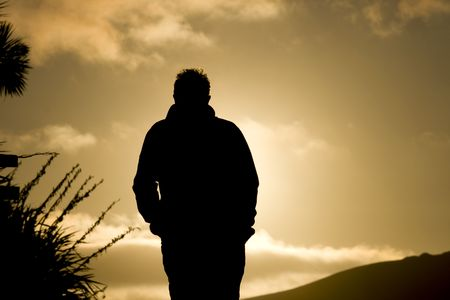 Man walking in sunset with hands in pocket. Black silhouette against sunlight