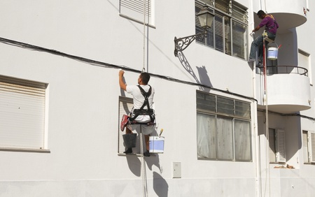 Two painters in harnasses working on a wall in Portugal