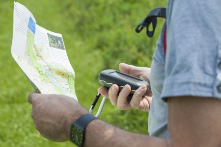 Man holding a GPS receiver and plan in his hand. Handheld GPS devices are used predominantly in the outdoor leisure industry for walking and hiking.