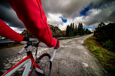 Cyclist on road bike through a asphalt road in the mountains and blue sky with clouds.