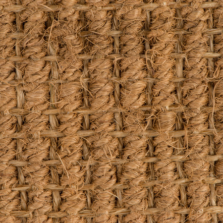 Closeup detail of a brown sisal carpet texture background.