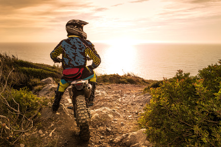 Enduro racer sitting on his motorcycle watching the sunset.