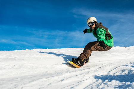Snowboard freerider in the mountains against in blue sky.