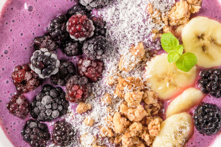 Healthy breakfast bowl: blueberry smoothie with banana, cococnut and blackberries.